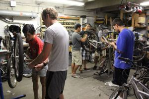 Valerie Do, head mechanic of OBP, helps show a member how to fix bicycles. Photo from OBP Facebook.