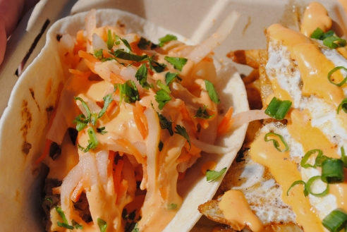 Check out that daikon! A closeup with The Peached Tortilla's braised pork belly banh mi taco and fries tossed with bacon jam, fried egg, Sriracha mayo and green onions.