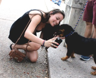 At the Puppy Petting Zone, Marysabel Cardozo takes a selfie with one of the dogs.
