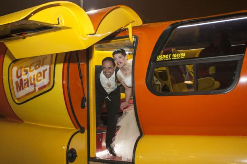 Newlyweds Jason Platt and Erin Lounsberry peek out the door of the Oscar Mayer Wienermobile before taking a post-wedding ride around the Quad-Cities on Friday night.