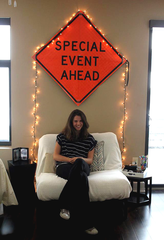 Hamilton sits in front of a key wall hanging in her apartment — a special event sign she scored off of the street.