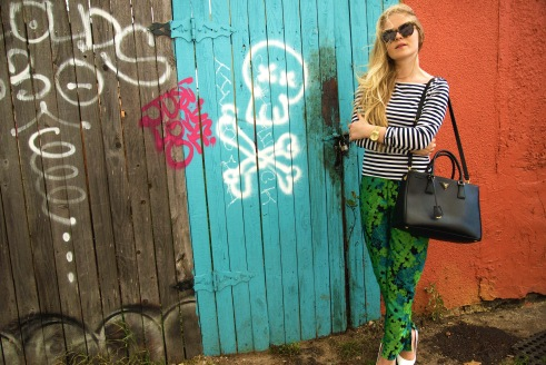 Froyland pairs her colorful ensemble with classic accessories, like white pumps and a black Prada bag.