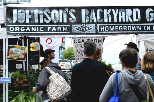 The community comes together as people pick out their produce and make their purchases at Johnson's Backyard Garden.