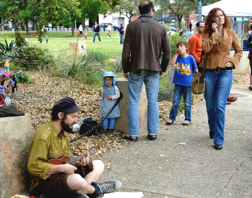 "A street performer sings ""Let it Be"" and strums his ukulele for passersby to enjoy."