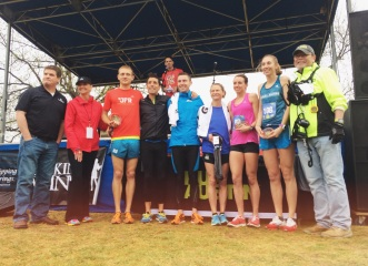 The winners of the Cap 10k pose for a group photo on the lawn of the Palmer Events Center.