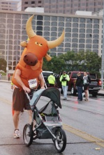 "With the help of the speaker blasting ""The Eyes of Texas"" in his stroller, Greg Meyers shows his longhorn pride while making his way to the starting line."