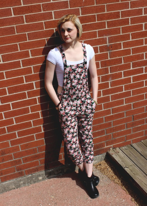 Jessica Grey poses in her floral overalls and a white crop top, both of which she purchased from Pacsun. She pairs them with black boots from Lucky Brand.