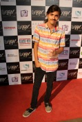 Attendee Eric Wade poses with drink in hand on the AFW red carpet.