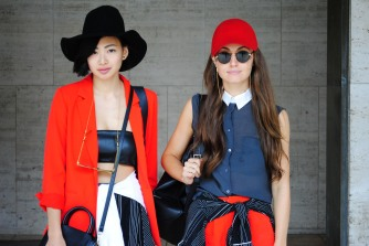 Alyssa Lau and Anna McDonough coordinate outfits with bright orange, white, and pinstripe black pieces. @alyyyssalauu
