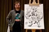 Matt Frank standing beside his winning drawing from the Kai-drew event.