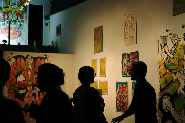 Guests attending the Raw Paw Canned Art Show and zine release discuss Sean Morgan's artwork.