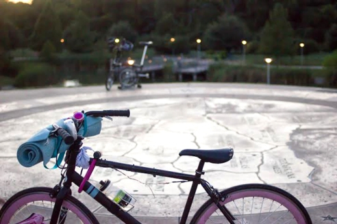 A bike rests atop Doug Sahm Hill with a yoga mat and a carved mural of Texas in the background.