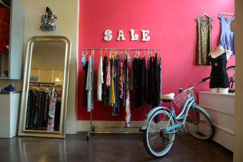 A rack of colorful sale items against a hot pink wall at the front of the boutique.