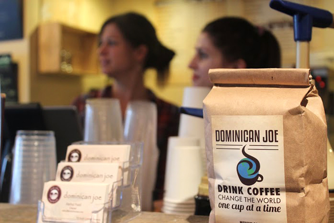 "Dominican Joe business cards and the shop's signature roast sit atop the front counter. Dominican Joe's motto is, ""Drink coffee, change the world one cup at a time."""
