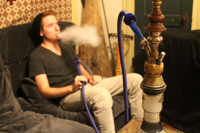 Kasbah Hookah Lounge manager Michael Davis tests a lemon mint-flavored hookah.