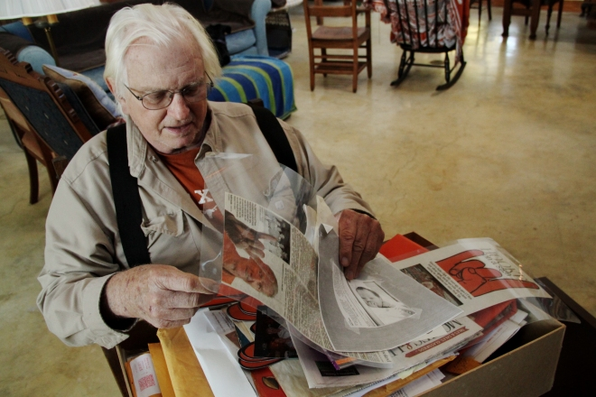 Clark looks through his box of memories. The large box is filled with newspaper clippings, pamphlets, and photos of his years as a UT legend.