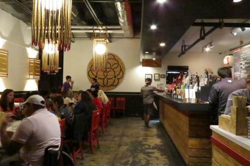 After entering, customers notice the large communal table responsible for a majority of seating in the small restaurant.
