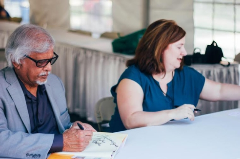Bethany Hegedus and Arun Gandhi at the signing tent autographing their book, Grandfather Gandhi.