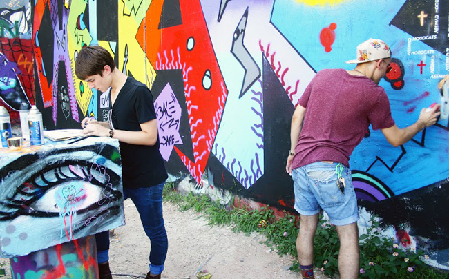 Richard Yates, left, works on a design on paper, while Ethan Cummins, right, uses spray paint to create a commentary piece at the Hope Outdoor Gallery in Austin on Oct. 9, 2014.