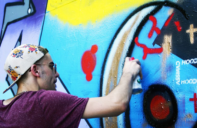 Ethan Cummins, a philosophy student at St. Edward's University, with can in hand, paints the vessels of an eyeball as part of a work commenting on the watchful eye of government on Oct. 9, 2014 at the Hope Outdoor Gallery in Austin.