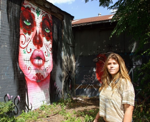 Molly Maroney, co-founder of SprATX stands beside two of her works. The painting of the women, modeled after a piece by artist Sylvia Ji, was done by Maroney and co-founder Mouf to spur others to create meaningful work on the walls behind SprATX's store in East Austin. Captured on Oct. 9, 2014.