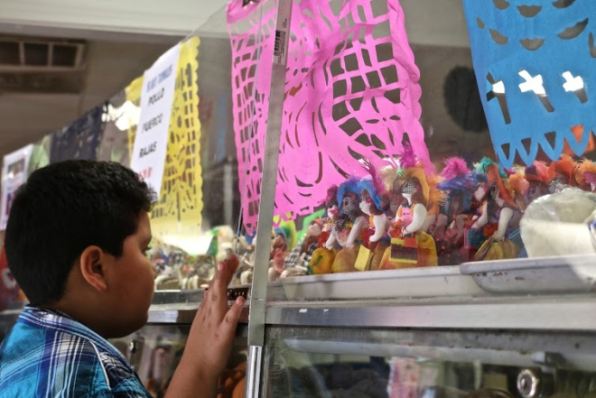 A boy peers into a case of sweets at La Mexicana Bakery.