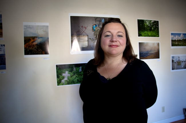 Photographer Cecily Johnson stands in front of her photographs at a gallery during the East Austin Studio Tour.