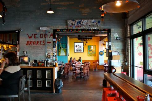 The cafe's decor is dynamic - yellow, blue, and orange walls with abstract, lively paintings