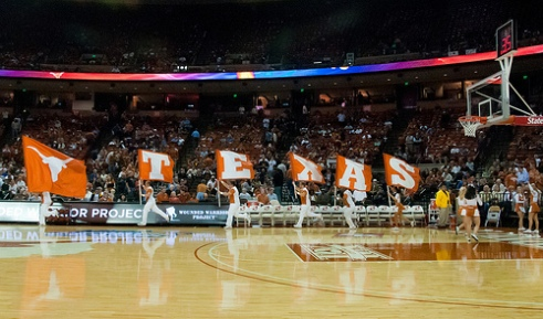 """Cheerleaders run flags that spell """"Texas"""" across the court before a University of Texas at Austin basketball game. 